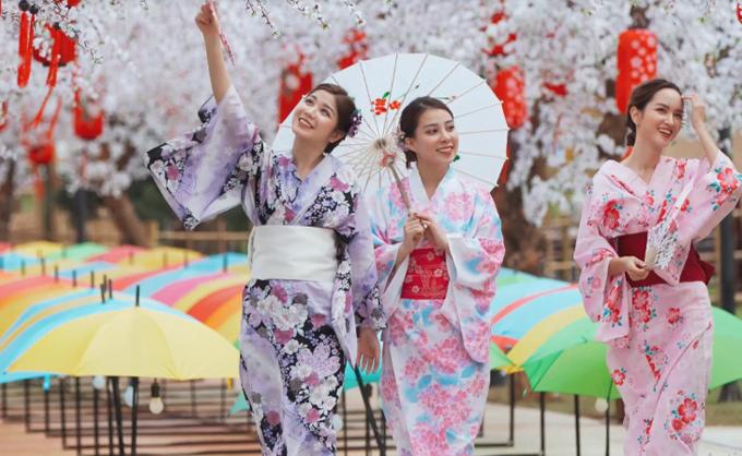 Các cô gái lạc bước trên đại lộ Hoa anh đào rực rỡ. Con đường này được các nghệ nhân hoa lụa nổi tiếng nhất Hà Nội hoàn thành trong hơn 2 tuần.