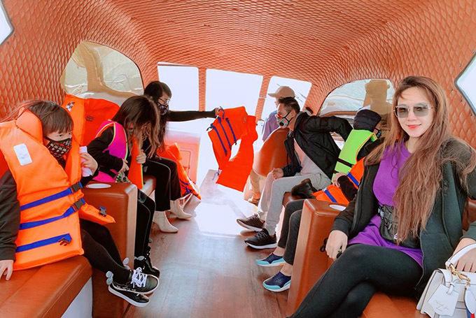Trên chuyến tàu tham quan vịnh Ninh Vân Lý Hải và các con cùng các hành khách khác vẫn đeo khẩu trang kín mít còn vợ anh - Minh Hà chỉ dám cởi ra chớp nhoáng để chụp ảnh kỷ niệm.