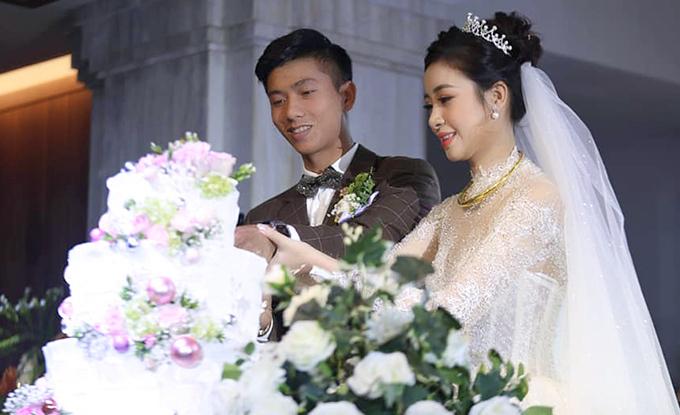 Vợ chồng Phan Văn Đức cắn bánh trong tiệc cưới. Ảnh: Oanh Oanh.