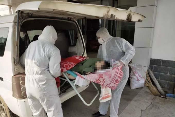 Các nhà chức trách đưa thi thể của Yan Cheng lên xe sau khi phát hiện em đã chết tại nhà ở huyện Hongan, Hồ Bắc. Ảnh: Wei Xin.