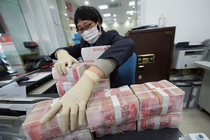 Một giao dịch viên tại ngân hàng ở tỉnh Giang Tô,Trung Quốc, đeo mặt nạ, mang bao tay nhận tiền từ khách hàng hôm30/1/2020. Ảnh: Reuters.