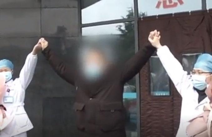 Chen vui mừng nắm tay các bác sĩ khi xuất viện sau thời gian ở trong khu cách ly của bệnh viện ở Vũ Hán. Ảnh: Pear Video.