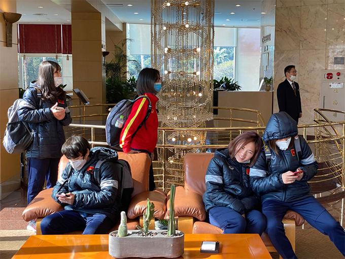 Các cầu thủ ngồi nghỉ tại sảnh khách sạn trong lúc chờ nhận phòng và ăn trưa