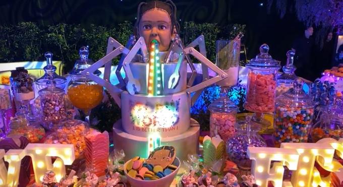 Chiếc bánh ga tô lớn đặt giữa những lọ kẹo in dòng chữ Hai tuổi phải khủng hơn một tuổi.