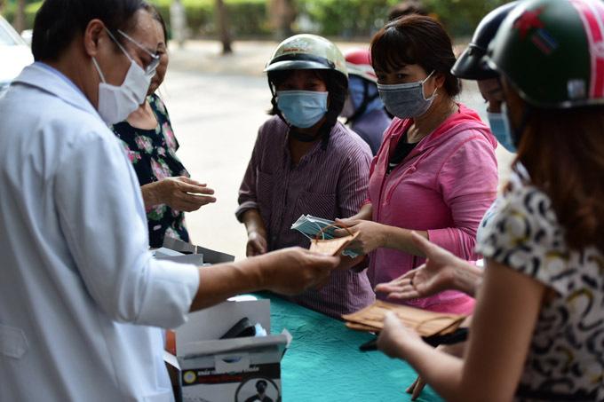 Người dân xếp hàng nhận khẩu trang từ đội ngũ nhân viên y tế của Viện thẩm mỹ Siam Thailand.