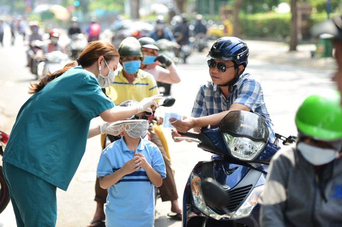 Nhân viên của Siam Thailand hướng dẫn người dân sử dụng khẩu trang đúng cách.