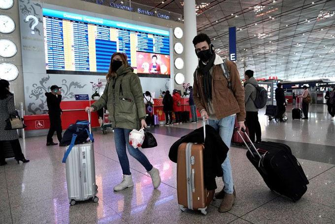 Người nước ngoài tháo chạy khỏi Trung Quốc tại sân bay Bắc Kinh hôm 1/2. Ảnh: Reuters.