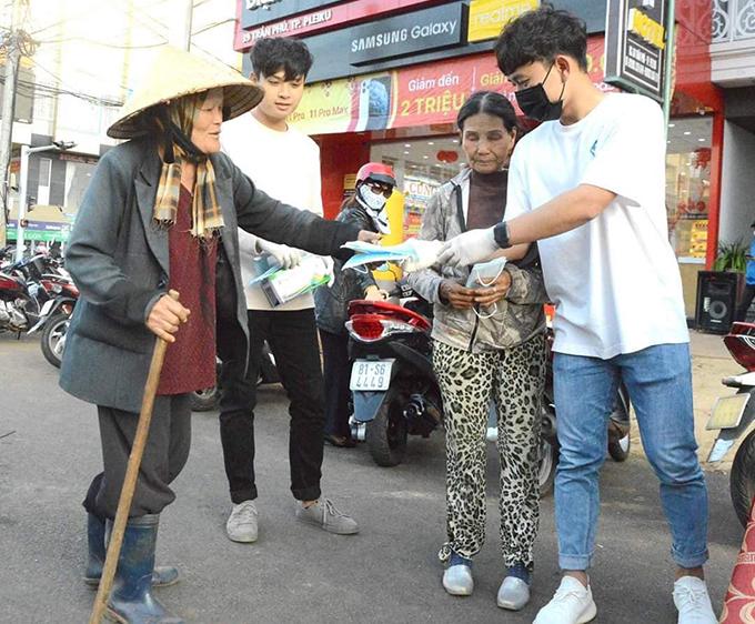 Tiền vệ Minh Vương (bìa phải) phát khẩu trang miễn phí cho người đi đường. Ảnh: Minh Vỹ.