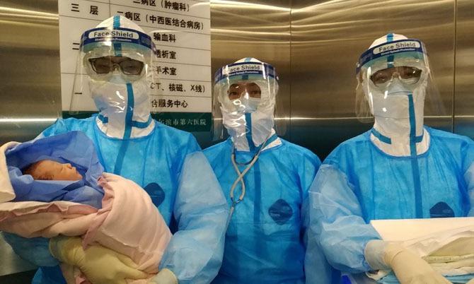 Bé gái được các bác sĩ cách ly với mẹ và chăm sóc ngay sau khi sinh hôm 30/1. Ảnh: China Daily.