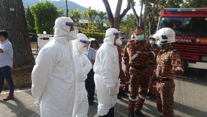 Cứu hỏa và nhân viên y tế đeo đồ bảo hộ tới lãnh sự quán Trung Quốc ở Penang, Malaysia hôm 31/1. Ảnh: Twitter.