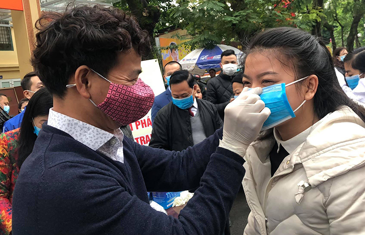 NSƯT Xuân Bắc đeo khẩu trang cho một bạn trẻ ở Hà Nội.