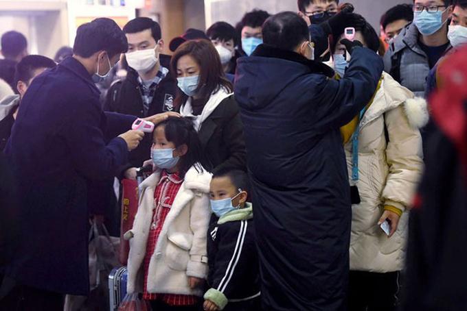 Người dân được kiểm tra thân nhiệt tại trạm tàu điện ngầm. Ảnh: Chinanews.