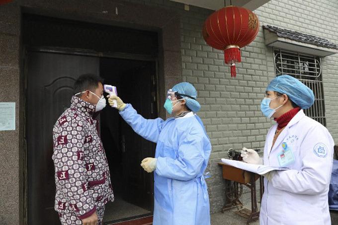 Một người đàn ông làm việc từ Vũ Hán trở về Hàng Châu nghỉ tết được các nhân viên y tế đến đo thân nhiệt tại nhà. Ảnh: AP.