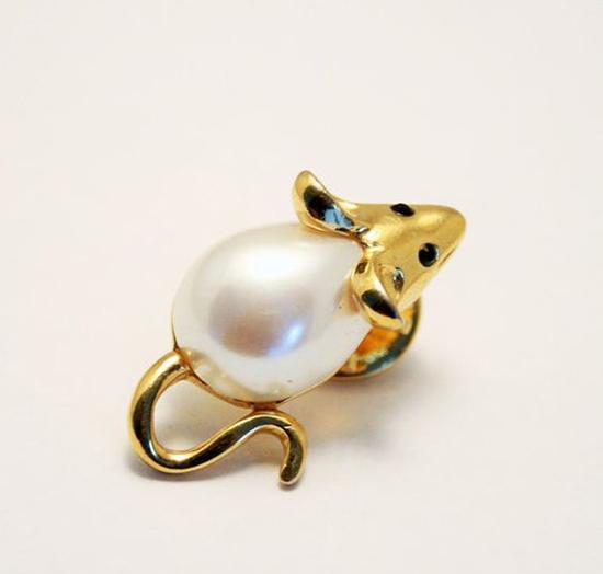Những chiếc cài áo nhỏ nhắnđược phối hợp giữa chất liệu vàng 18k, hạt ngọc trai để tạo nên hình ảnh chú chuột vàng may mắn.