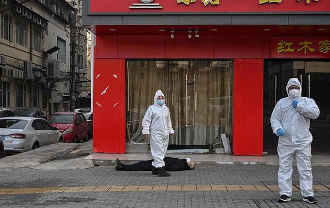 Các nhân viên y tế được gọi tới để đưa xác một người đàn ông chết trên đường phố Vũ Hán hôm 30/1. Ảnh: AFP.