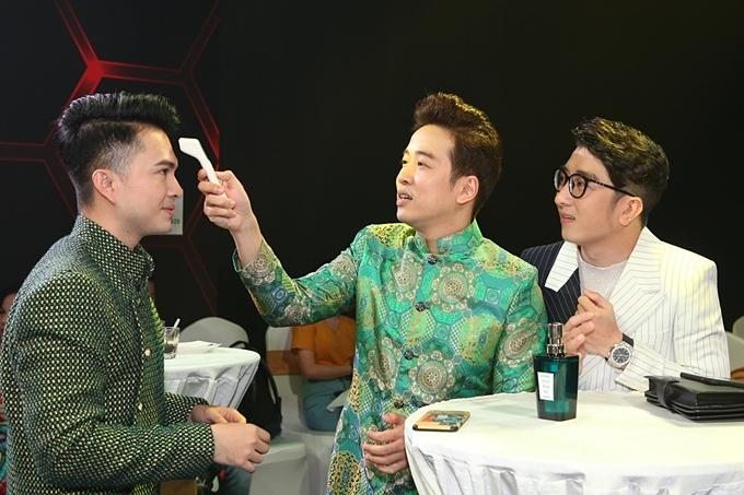 Ca sĩ Nam Cường (trái) được Triệu Lộc (giữa) kiểm tra thân nhiệt.