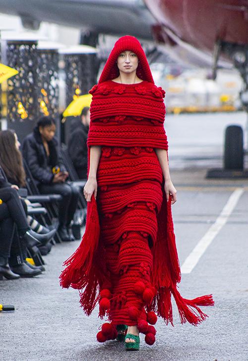 Váy len trở nên độc đáo bởi hàng trăm cánh hoa mai cùng tông màu được trang trí dọc thân váy. Kết hợp cùng khăn choàng tua rua, người mẫu trở nên nổi bật và ấn tượng trong từng chuyển động.