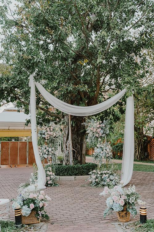 Cổng hoa được dựng đơn giản theo kiểu ngẫu hứng với tấm lụa trắng, bên cạnh là các giỏ hoa Ohara.