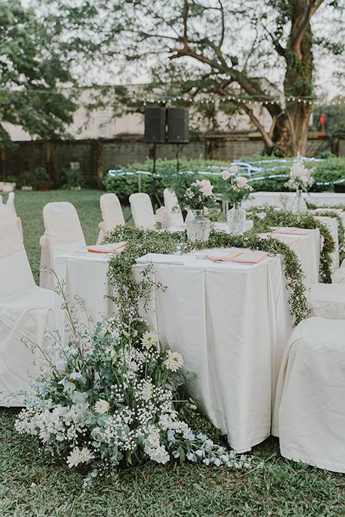 Uyên ương chọn bàn chữ nhật và ghế banquet cho không gian. Ở thân ghế được thắt dải lụa hồng pastel - tông màu chủ đạo của buổi tiệc.