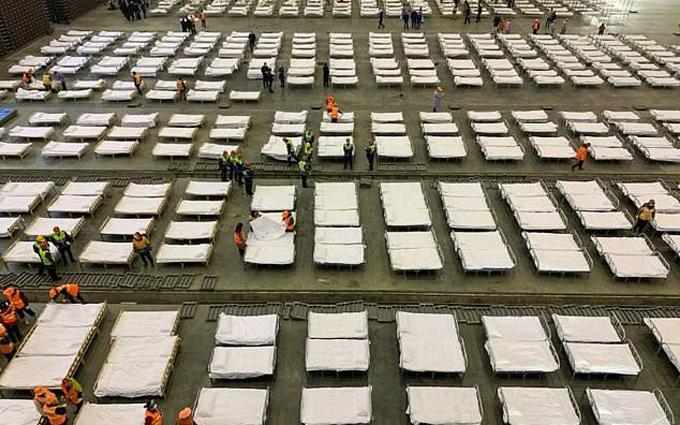Nhân viên bố trí giường sau khi một trung tâm triển lãm được chuyển thành bệnh viện tạm thời ở Vũ Hán, Hồ Bắc. Ảnh: AFP.