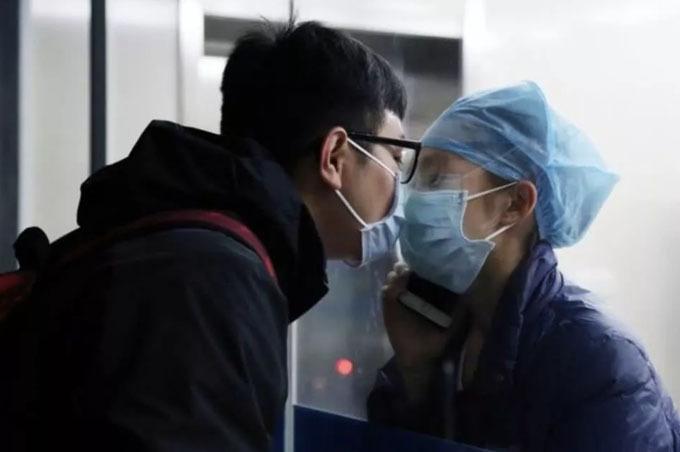 Hai người trao nhau nụ hôn qua kính trong cuộc gặp mặt tối 4/2. Ảnh: QQ.