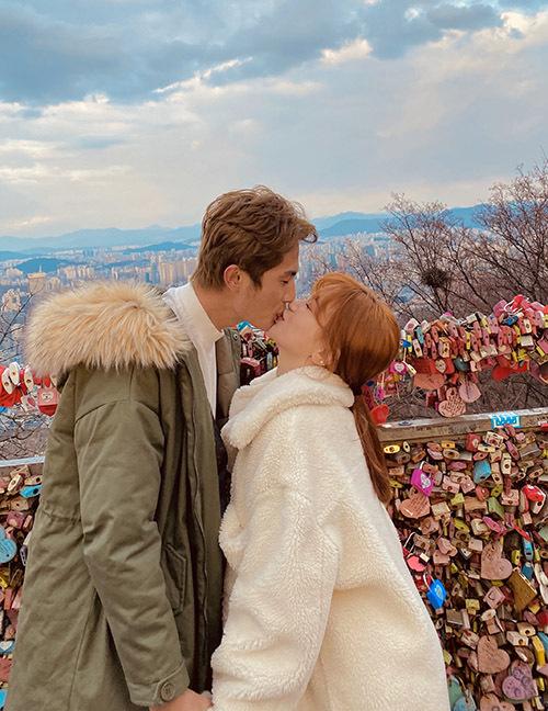 Cặp đôi say đắm hôn nhau trên câu cầu treo dày đặc những ổ khoá tình yêu đủ sắc màu.