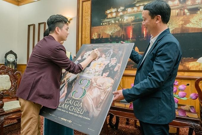 Đạo diễn Bảo Nhân (trái) và các thành viên ký tên lên poster phim đểtặng đại diện lãnh đạo tỉnh.
