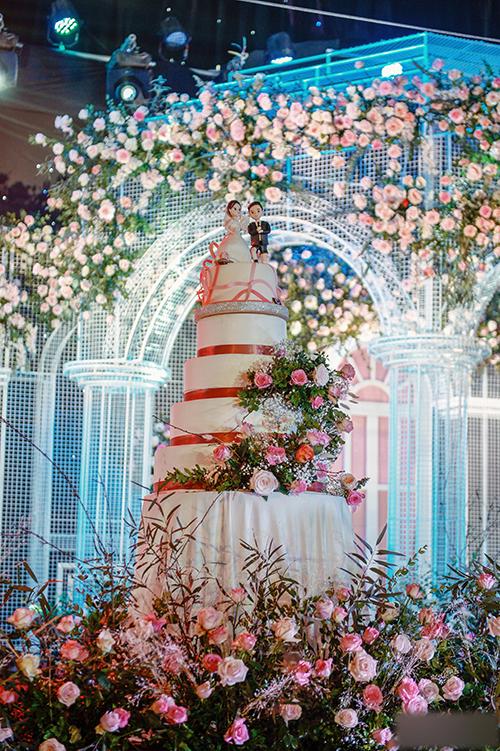 Bánh cưới trắng được tô điểm với hoa tươi và tượng mô phỏng 2 vợ chồng Quỳnh Anh - Duy Mạnh.