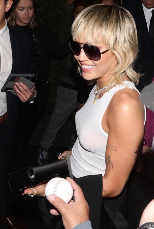 Miley rạng rỡ khi đến dự tiệc. Nữ ca sĩ đi thẳng tới sự kiện này sau khi tham dự show thời trang Tom Ford vào đầu giờ tối.