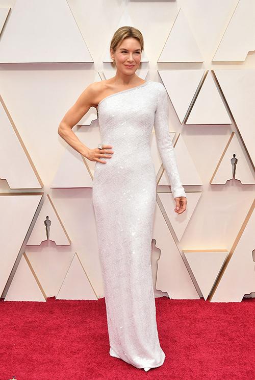 Váy trắng Armani Prive phủ kim sa mang kiểu dáng tối giản nhưng dựng phom khéo léo đem lại cho Renee Zellweger - chủ nhân tượng vàng Nữ diễn viên chính xuất sắc năm nay - vẻ thanh lịch, trang nhã.