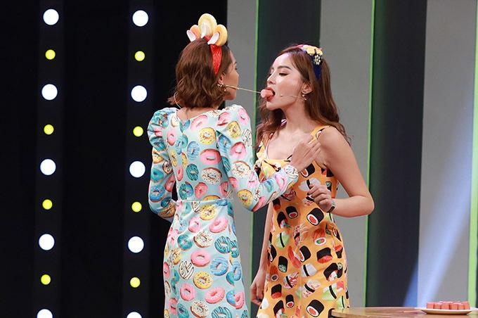 Hai người đẹp tham gia thử thách chuyền xúc xích bằng miệng. Họ phối hợp ăn ý, được mọi người cổ vũ nồng nhiệt.