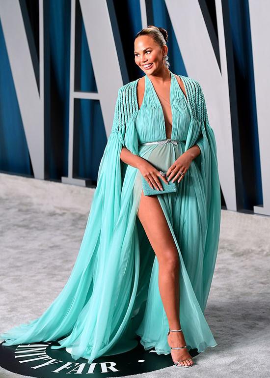 Người mẫuChrissy Teigen mặc váy xẻ cao, khéo che chắn bằng chiếc bóp cùng màu.