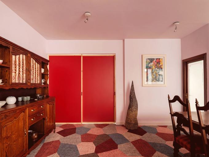 Nhà được quy hoạch thành các phòng chức năng: nhà bếp - phòng giặt, phòng dành cho hoạt động nghệ thuật và phòng khách. Gia chủ chọn lựa đồ gỗ màu tối, gợi nhắc chút xưa cũ của căn hộ. Thảm sàn mang sắc đỏ đậm phối với các màu phụ trợ giúp tăng giá trị thẩm mỹ của căn hộ.