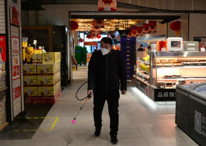 Một nhân viên đeo khẩu trang xịt chất khử trung tại cửa hàng 7Fresh của JD.com tại khu Yizhuang, Bắc Kinh, hôm 8/2 trước khi mở cửa trở lại. Ảnh: Reuters.