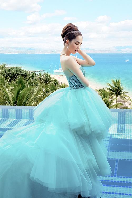 Đầm dạ hội được kết hợp giữa vải sequins cho phần cúp ngực và chân váy xếp tầng bồng bềnh bằng nhiều lớp vải tuyn ton-sur-ton.