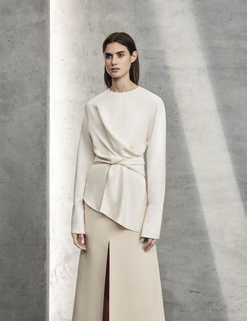 Áo nhấn eo được thiết kế tinh tế với cách sử dụng kỹ thuật draping tạo đường xoắn vải nhẹ nhàng trên áo suông.