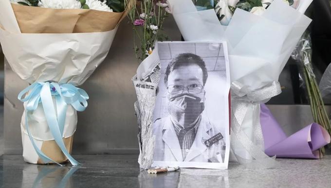 Những bó hoa cùng ảnh của bác sĩ Lượng được đặt bên ngoài Bệnh viện Trung ương Vũ Hán, nơi anh làm việc. Ảnh: EPA.