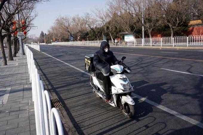Một nhân viên giao hàng trên đường phố hiếm người qua lại ở Bắc Kinh hôm 31/1. Ảnh: AFP.