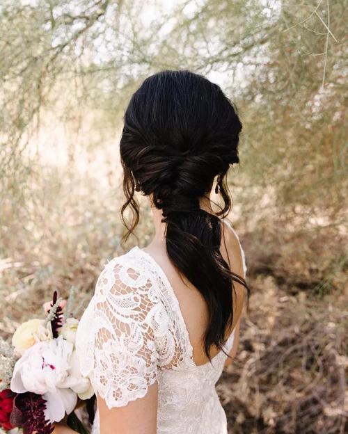 Tóc tết xoắn, lỏng ở phần đuôi. Lọn tóc mái được thả rơi giúp hoàn thiện vẻ ngoài của cô dâu chuộng phong cách boho, rustic.