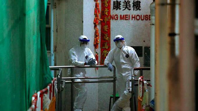 Nhân viên mặc đồ bảo hộ đứng kiểm soát ở trước lối vào chung cư Hong Mei House, Hong Kong, sáng 11/2. Ảnh: AP.