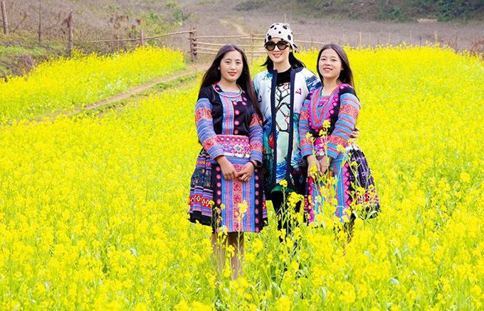 Giáng My chụp ảnh cùng hai cô gái diện váy thổ cẩm sặc sỡ, dạo chơi cánh đồng hoa cải.