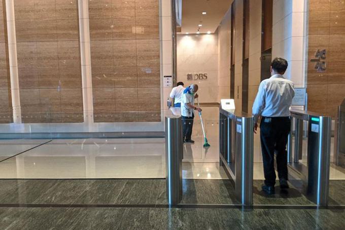 Nhân viên vệ sinh lau dọn trụ sở Ngân hàng DBS tại Trung tâm Tài chính Mariana Bay, Singapore. Ảnh: Straistimes.