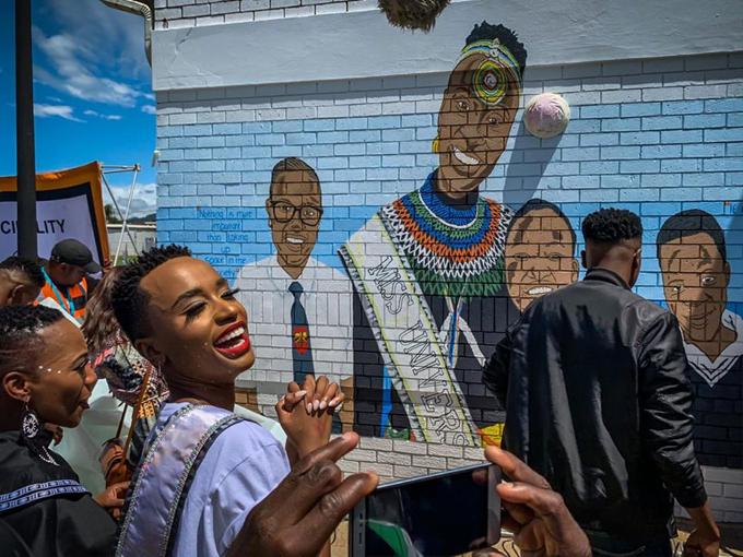 Cô rất bất ngờ trước bức tường in hình ảnh của mình trong chiếc áo truyền thống Nam Phi.