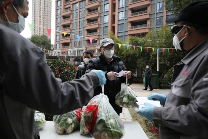 Nhân viên xã hội chia rau cho các hộ gia đình ở Vũ Hán, tỉnh Hồ Bắc hôm 11/2. Ảnh: Reuters.