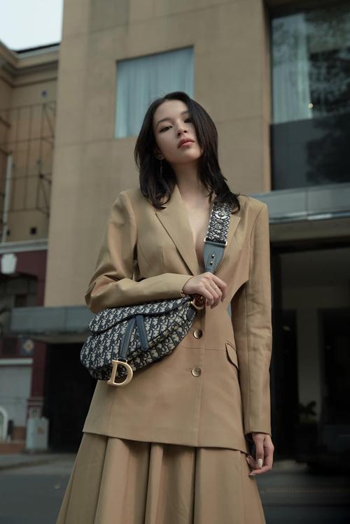 Chọn blazer phá cách với đường cut-out độc đáo phần eo thon, Phí Phương Anh hoàn thiện set đồ bằng túi Dior sang chảnh.