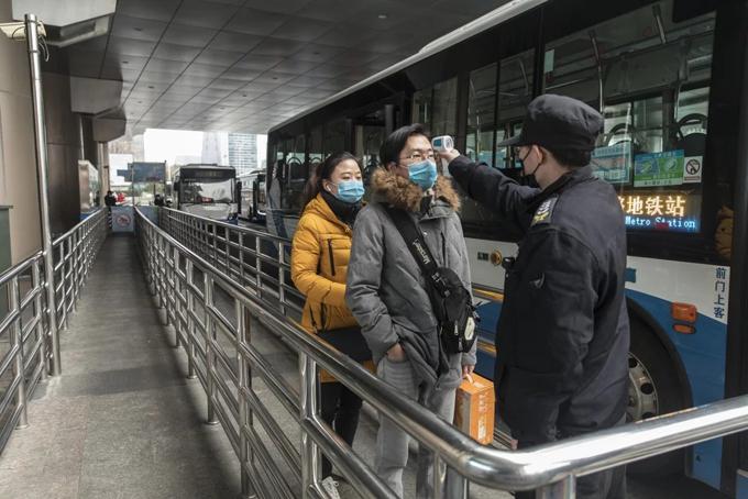 Người lao động di chuyển về thành phố bị kiểm tra nhiệt độ khi đi qua các trạm kiểm soát giao thông. Ảnh: SCMP.