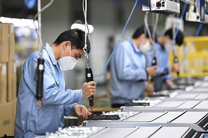Công nhân đeo khẩu trang bảo hộ trong một nhà máy điện tử ở Thâm Quyến, Trung Quốc. Ảnh: Xinhua.