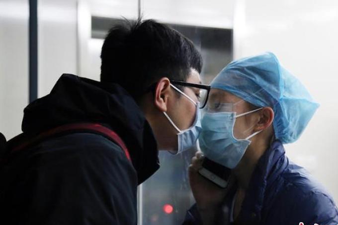 Y tá Chen Ying và bạn trai Huang Qianrui hôn nhau qua tấm kính cách ly ở bệnh viện Đại học Y Khoa tỉnh Chiết Giang. Ảnh: CNNews.