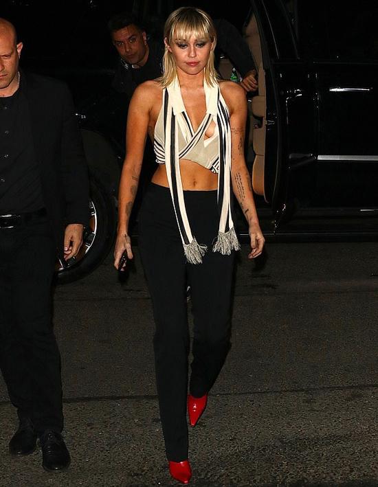 Cô mặc chiếc áo có đường cắt xẻ phóng khoáng và dễ xô lệch khi di chuyển.