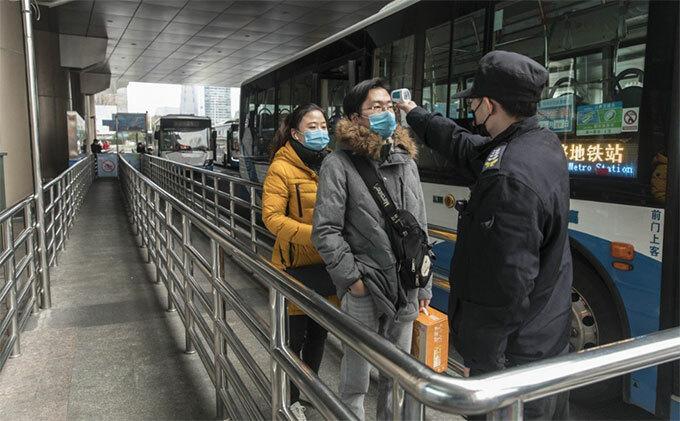 Hành khách được kiểm tra thân nhiệt trước khi lên xe buýt ở Thượng Hải. Ảnh: Bloomberg.